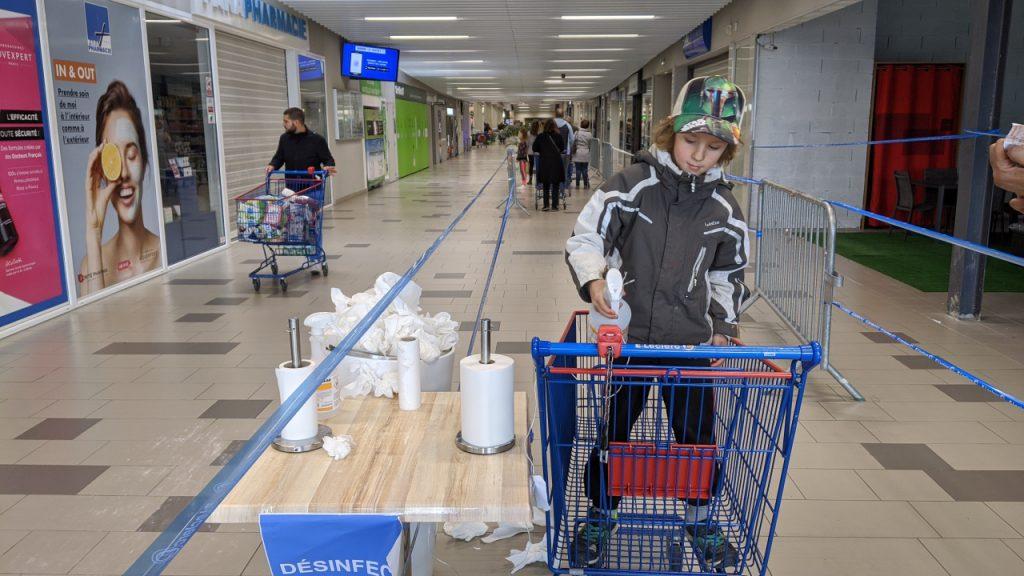 Ein Junge desinfiziert mit einem Reinigungsspray einen Einkaufswagen in einem Supermarkt. Dazu hat er sich in den Einkaufswagen begeben. Im Hintergrund ist eine Warteschlange mit Menschen, die den Supermarkt betreten möchten.