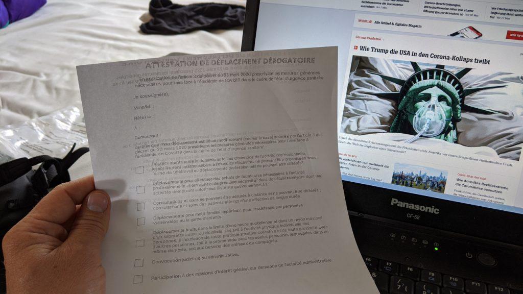 Foto einer französischen Corona Attestation, die für die Reise benötigt wird. Im Hintergrund ist ein Notebook, auf dem eine Online Webseite über Trump und Corona in den USA berichtet