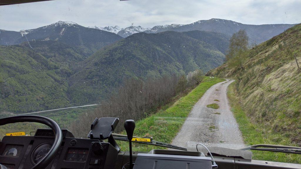 Blick aus dem Cockpit vom Truck auf einen sehr engen Feldweg, der eigentlich zu klein für das Fahrzeug ist. Im Hintergrund sind schneebedeckte Berge.
