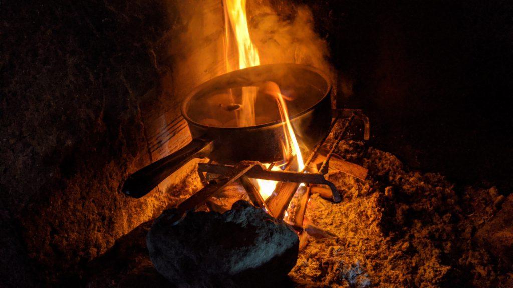 Ein Topf Kartoffeln kocht auf einem Lagerfeuer in einer Schutzhütte im Aston Tal, kurz vor der Grenze zu Andorra.