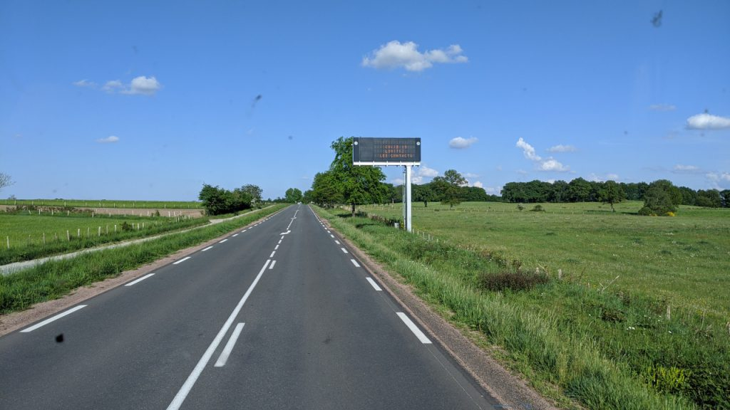 Eine leere Landstrasse in Frankreich mit einer Covid 19 Strassen Anzeige