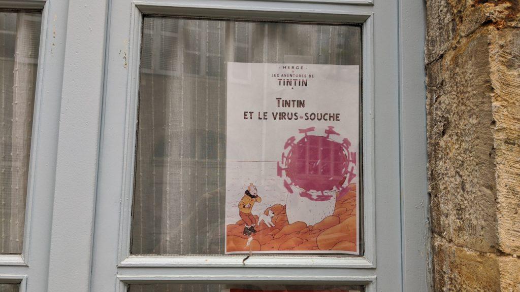 Ein Fenster, was ein abgewandeltes Plakat für Tim und Struppi zeigt. Tintin, das ist der französische Name für Tim und Struppi, betrachtet ein Corona Virus.