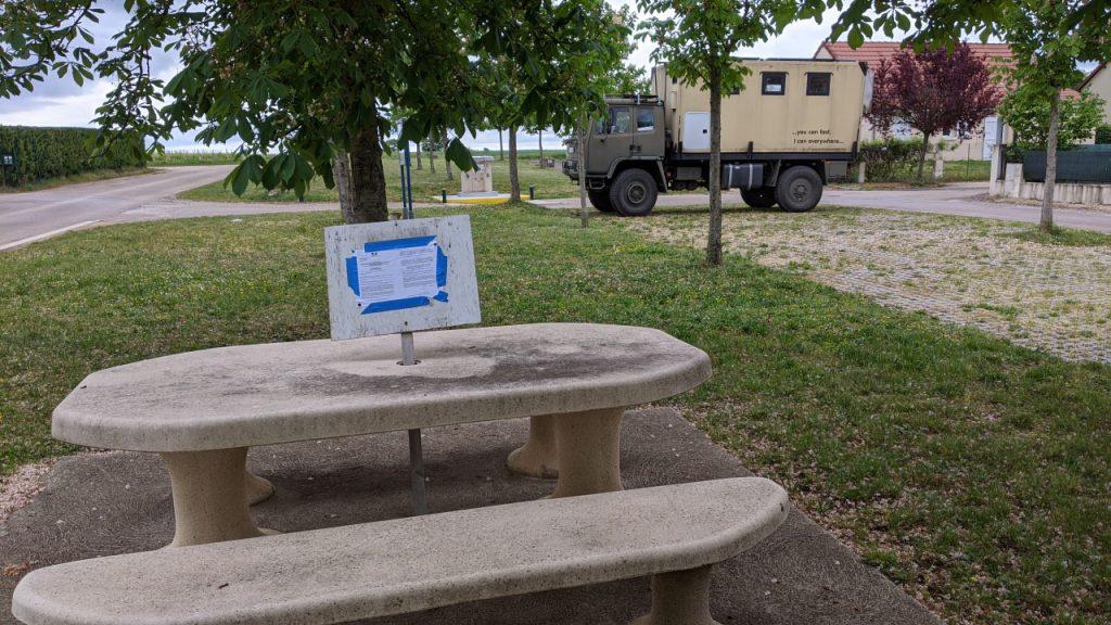 Ein Rastplatz mit Sitzmöglichkeit, dieser ist für die Benutzung wegen Corona gesperrt, worauf ein Schild hinweist. Im Hintergrund ist ein DAF T244 LKW.