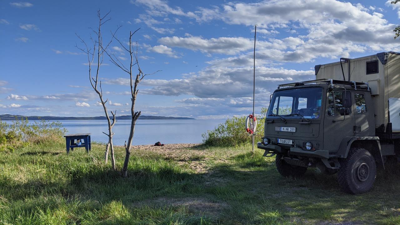 Ein Lagerplatz mit Tisch und an einem See in Schweden, rechts steht der DAF T244 Truck