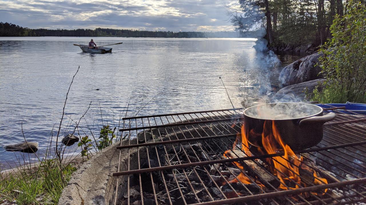 Ein Topf mit Kartoffeln kocht in Schweden auf einem kleinen offenen Feuer an einem See. Auf dem See fährt ein 15 jähriger Junge Ruderboot.
