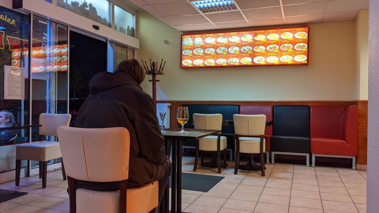 Ein Mann sitzt mit einem Parka bekleidet in einem Chinaimbiss, er scheint der einzige Kunde zu sein. Die Eingangstür ist blockiert und   steht permanent offen.