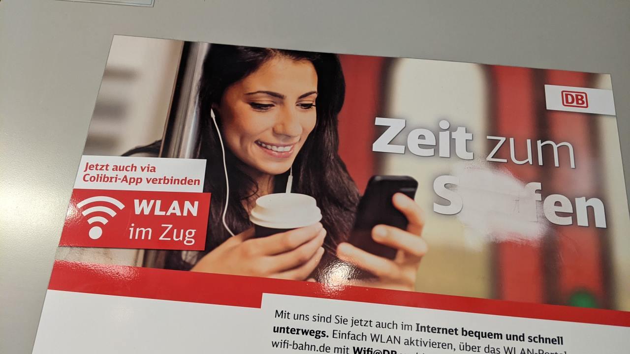 Ein Werbeplakat der Deutschen Bahn welches die Benutzung von WLAN im Zug empfiehlt. Ungewöhnlich ist die Abbildung einer Frau ohne Maske.