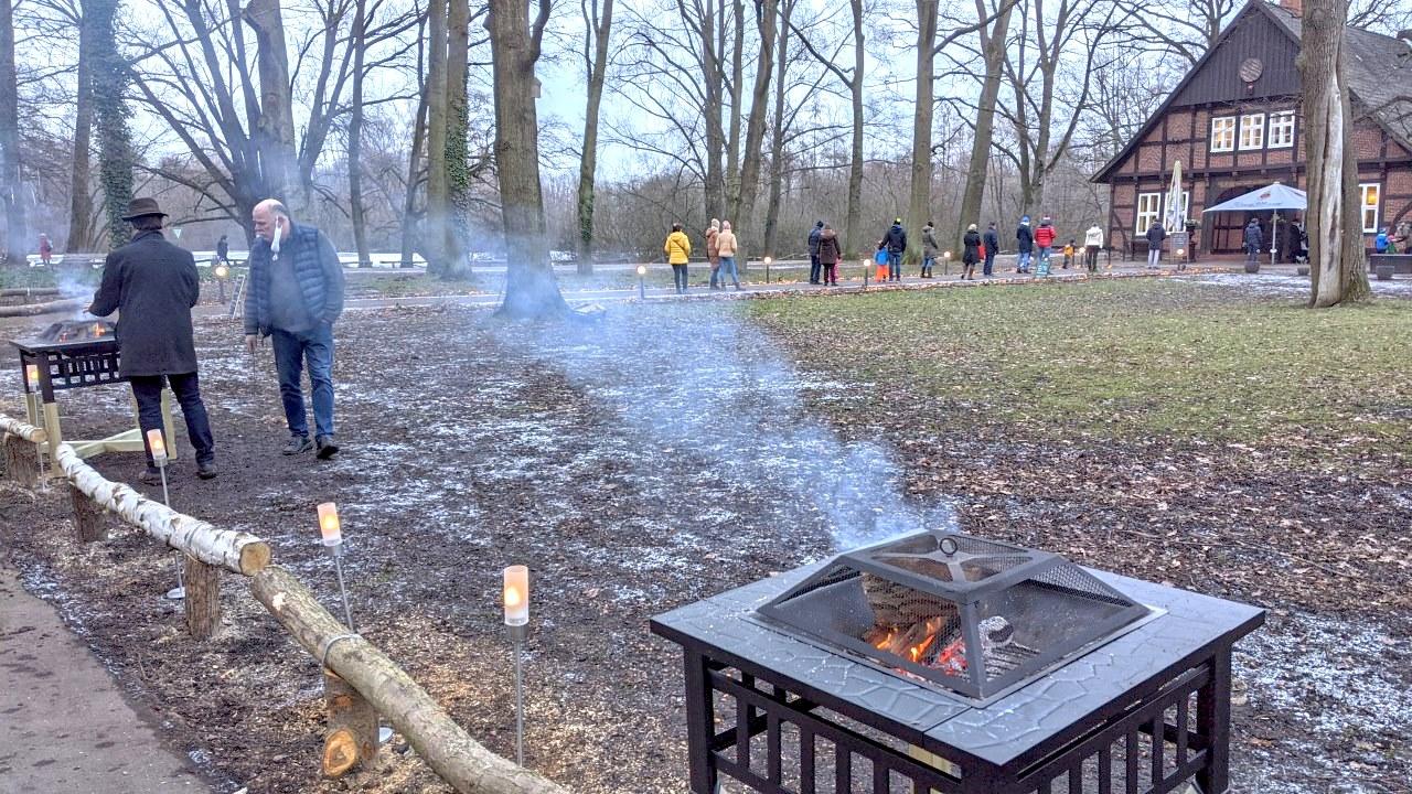 Am Wegrand im Annapark Hannover sind kleine Holzöven aufgebaut, etwas Rauch zieht durchs Bild. Im Hintergrund stehen Menschen in einer Schlange, um Snacks und heiße Getränke zum mitnehmen zu kaufen.