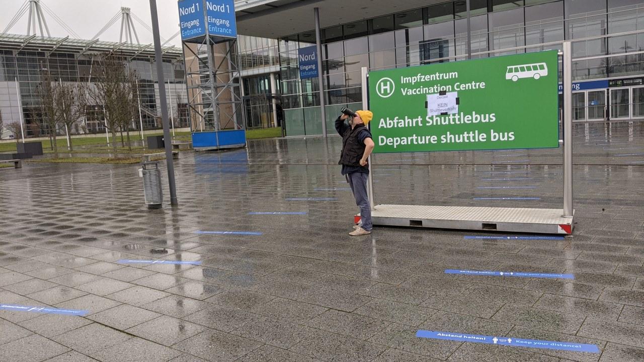 Ein Mann hält vor dem Corona Impfzentrum Hannover neben einem Hinweis Schild zu Shuttle Bussen mit einem Fernglas nach etwas ausschau. Das Gelände ist leer und verlassen.