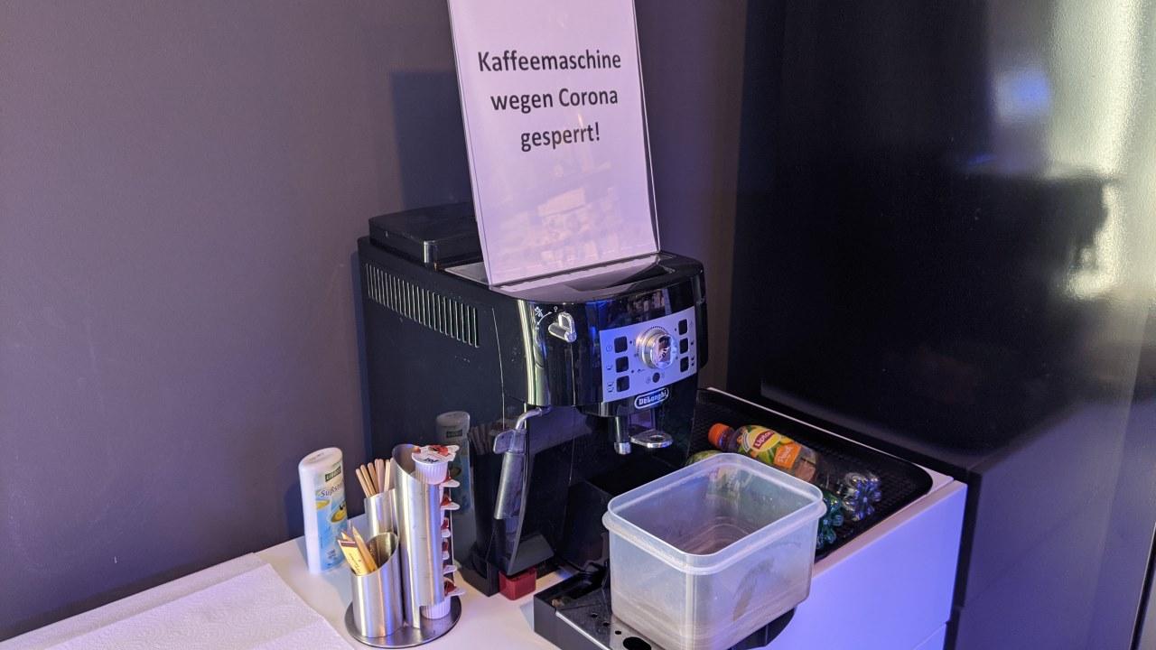 Eine Kaffee Vollautomat, der wegen Corona ausser Betrieb ist. Darauf weist ein Schild über der Kaffeemaschine hin.