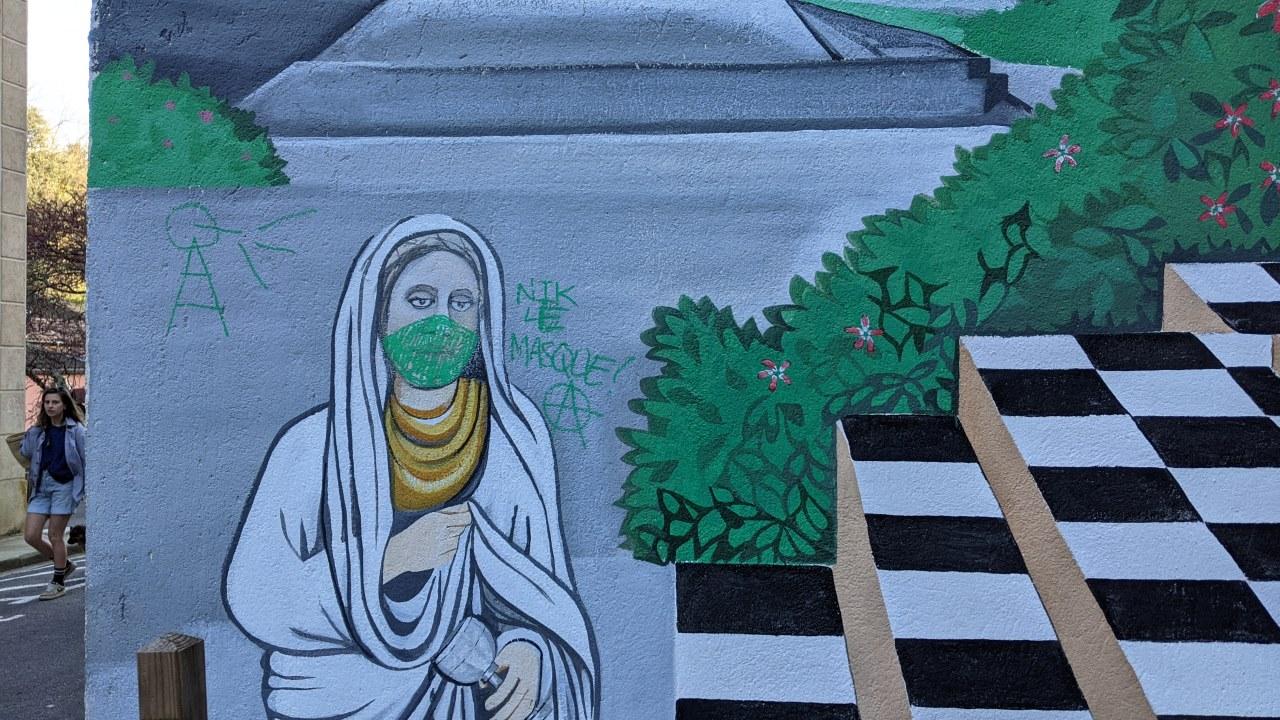 Eine Wandmalerei in Rennes-le-Bains Frankreich. Die Abbildung einer Frau mit weissem altertümlichen Gewand wurde um eine aufgemalte grüne Corona Maske ergänzt.