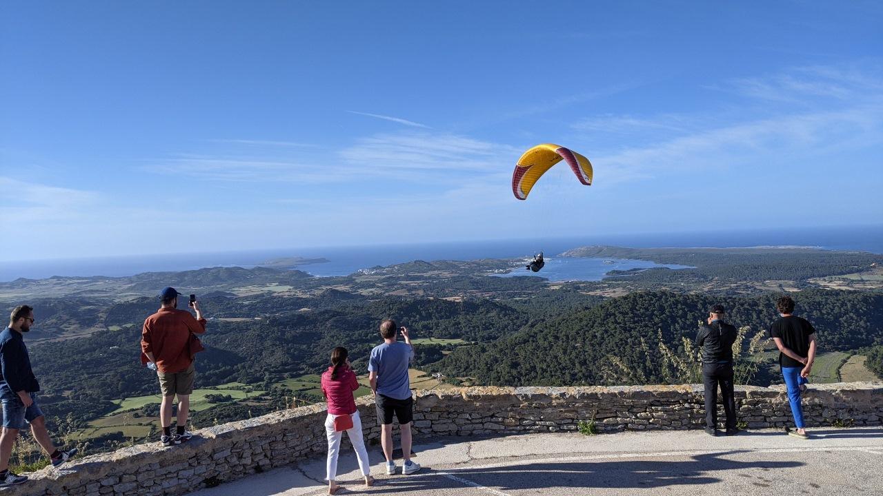 Menschen beobachten einen Gleitschirmflieger Paraglider auf dem Berg del Toro auf Menorca