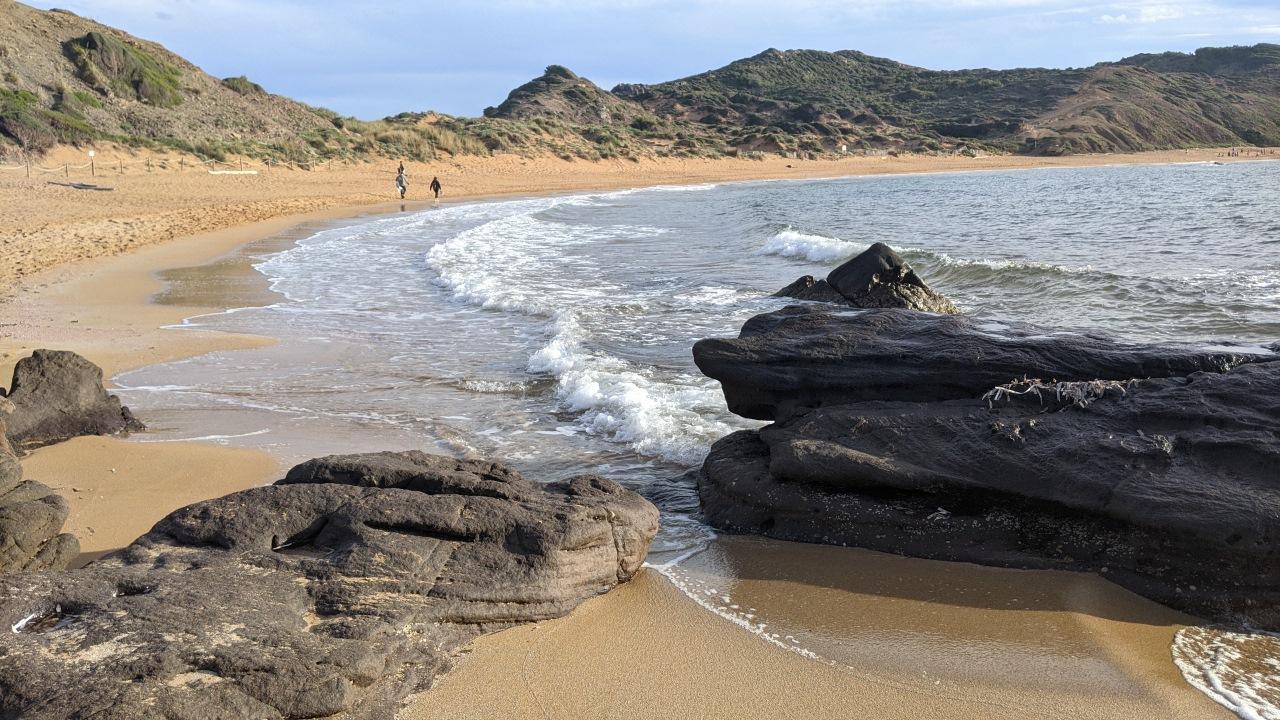 Das Bild zeigt den Strand Platja de Cavalleria im Norden Menorcas mit Felsen im Vordergrund und ein paar Spaziergängern