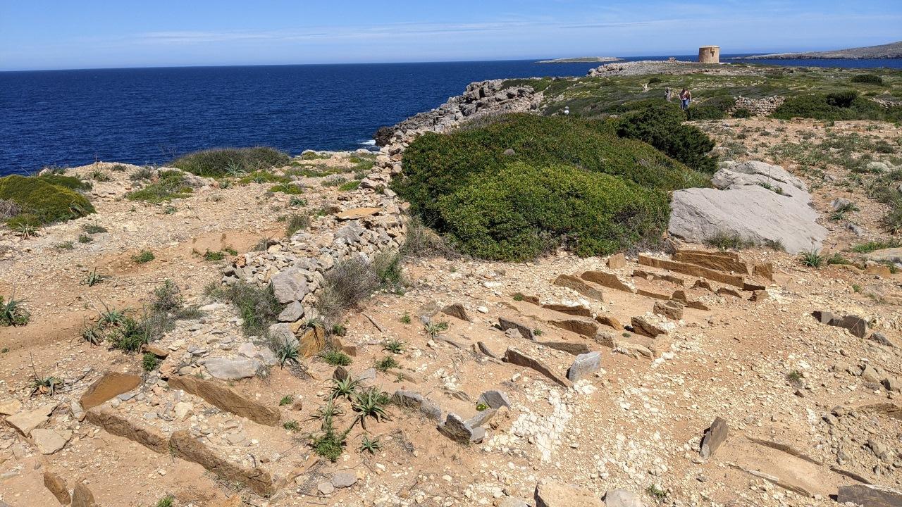 Ein römischer Friedhof in Cape Cavalleria auf Menorca, das Bild zeigt Gräber am Rande des blauen Meers