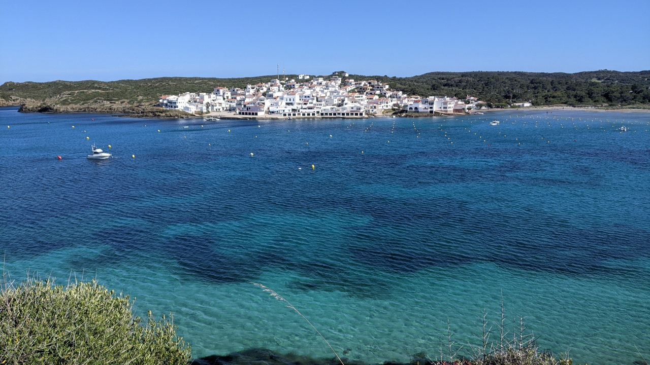 Der Ort Es Grau auf Menorca, im Vordergrund ist türkis blaues Wasser