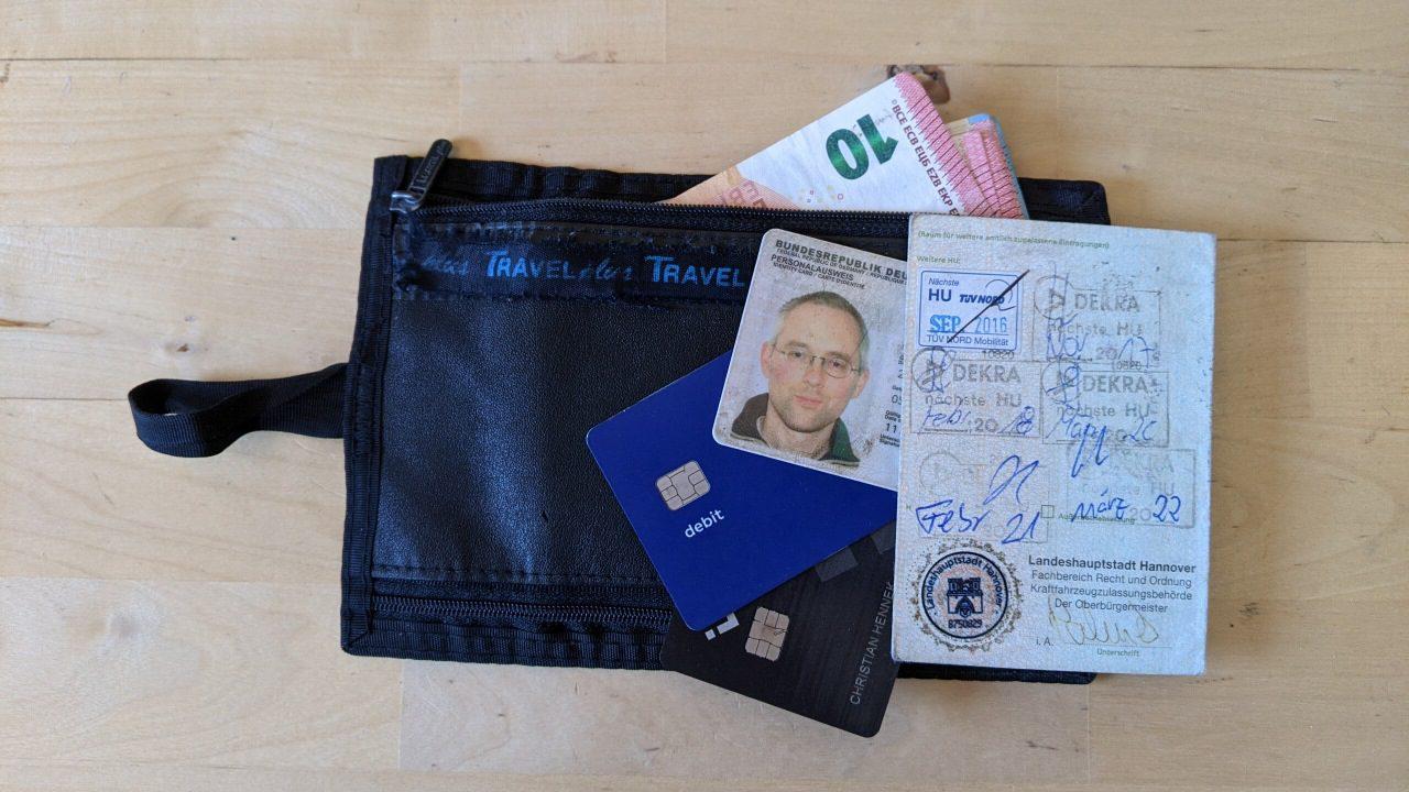 Gürtelinnentasche, der Inhalt ist auf der abgelegten Tasche abgebildet: ein Perso, zwei Kreditkarten, Fahrzeugpapiere und etwas Bargeld