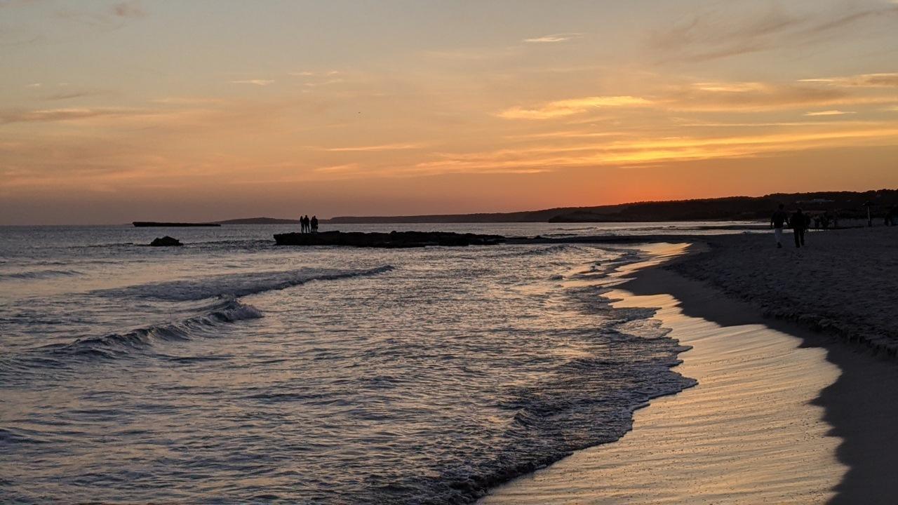 Sonnenuntergang auf Menorca, Menschen blicken von einem Felsvorsprung aufs Meer während die Wellen an den Strand laufen