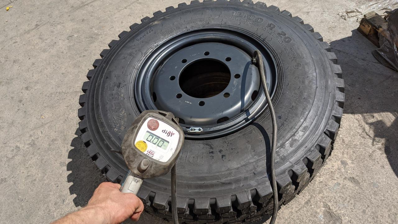 Ein frisch montierter 12.00R20 LKW Reifen wird mit Druckluft aufgepumpt und gemessen