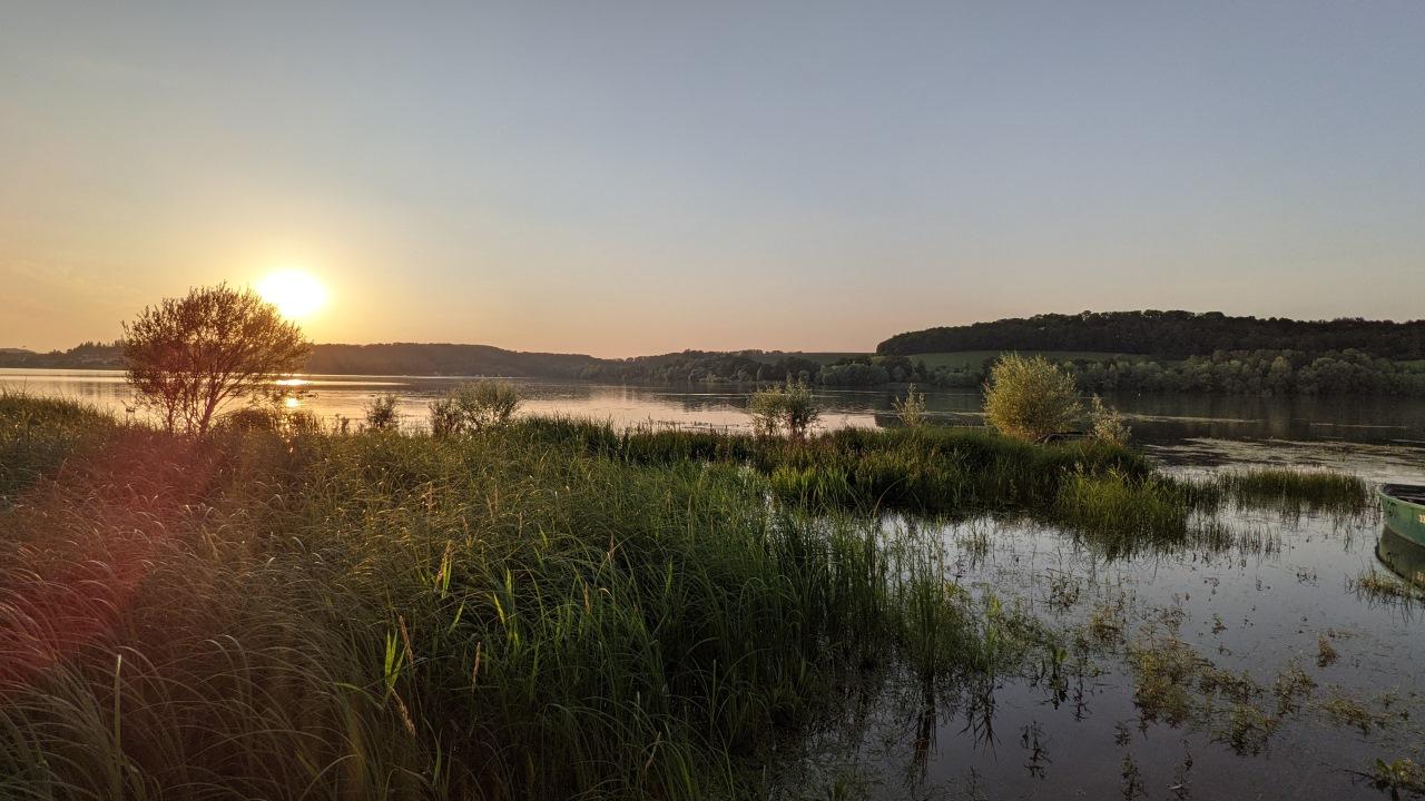 Sonnenuntergang am Lac de la Liez bei Langres. Die Abendsonne scheint auf die Uferböschung.