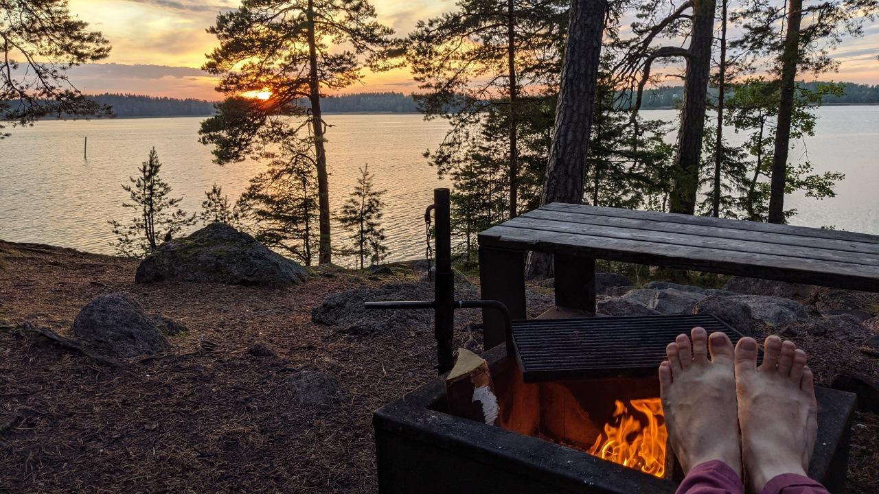 Ein finnischer Rastplatz mit Feuerstelle und Blick auf einen See. Ich wärme mit am Feuer die nackten Füße.