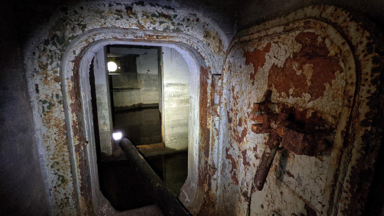 Unter Wasser stehender Bunker der Salpa Linie Finnland mit Blick in den Innenraum und verrosteter Tür