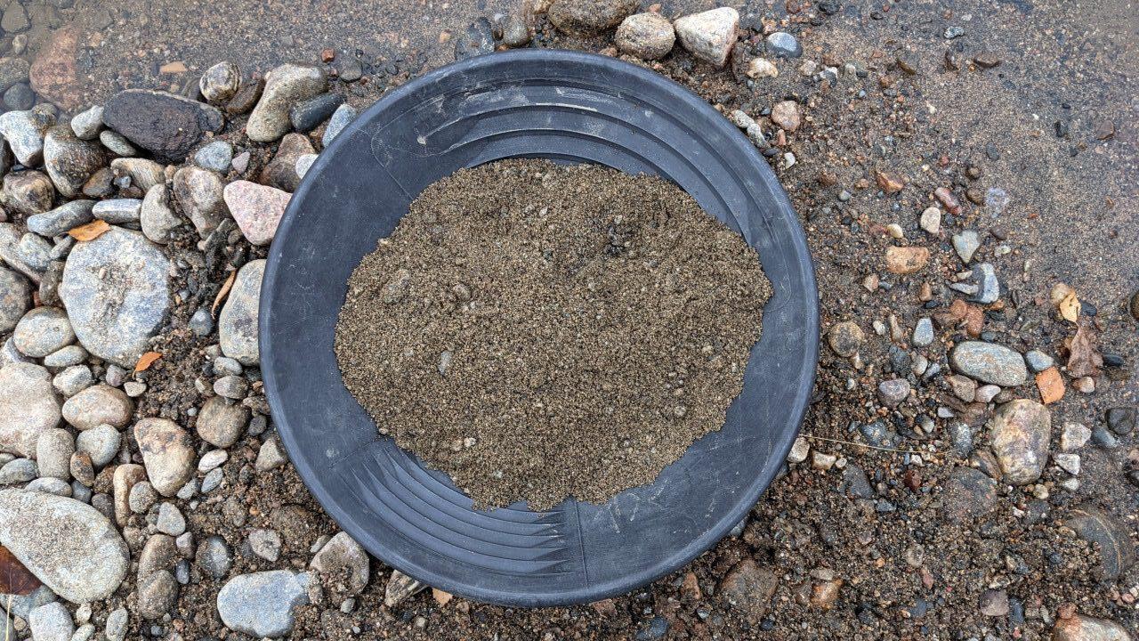 Mit frischem Sand gefüllte Goldwaschpfanne