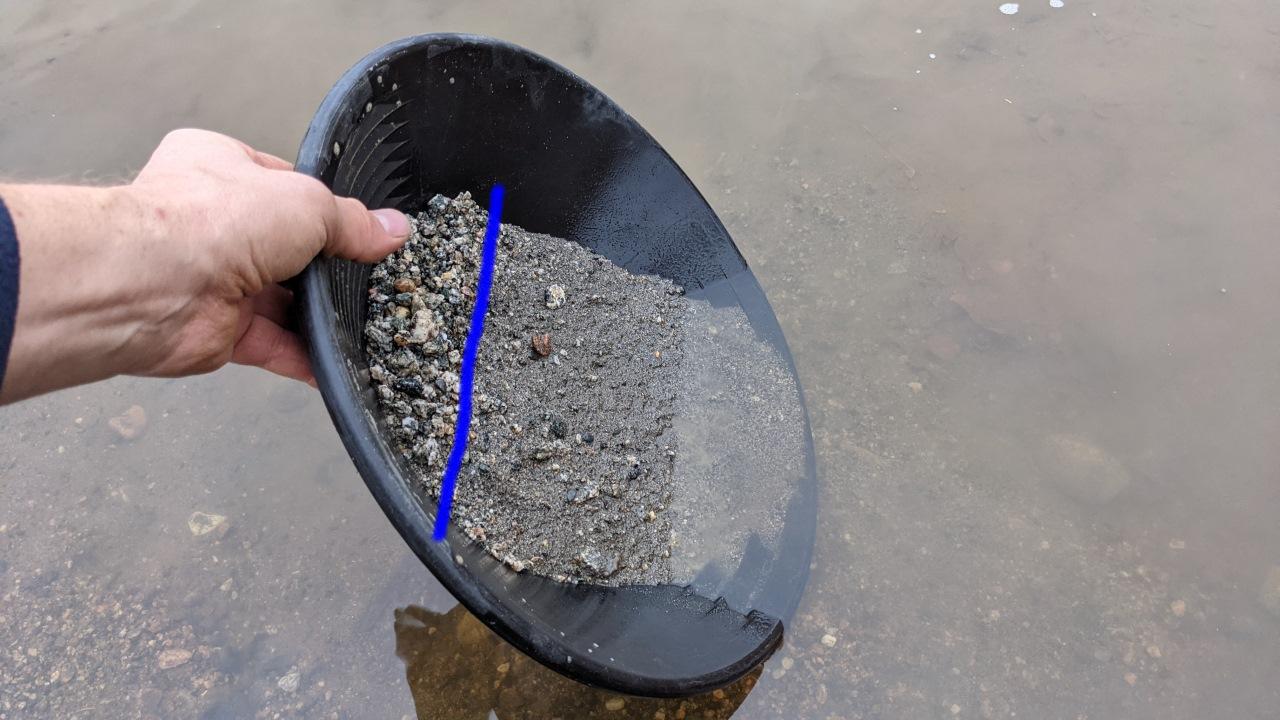 Noch mehr Sand wird in der Goldwaschpfanne ausgewaschen