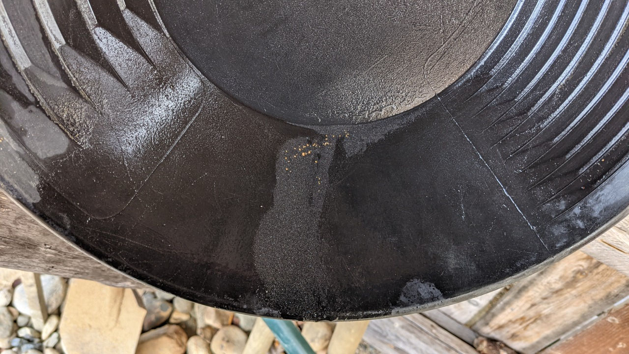 Gold wird am Boden der Goldwaschpfanne sichtbar