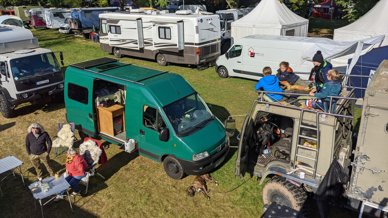 Überblick über die OTTO Touristik Messe Ohrdruf mit unterschiedlichen Fahrzeugen. Vier Kinder haben es sich auf einem DAF T244 gemütlich gemacht.